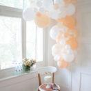 Une guirlande de ballons dans les tons peach et blanc