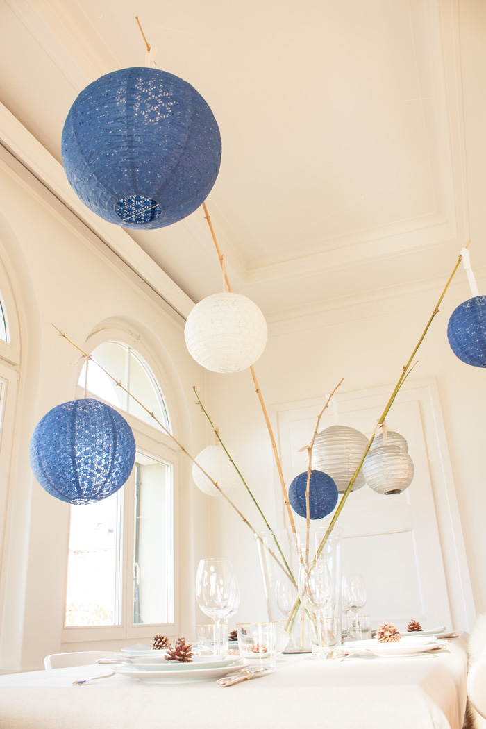 Un décor de noël scandinave bleu et argenté avec des lanternes dentelle et chinoise