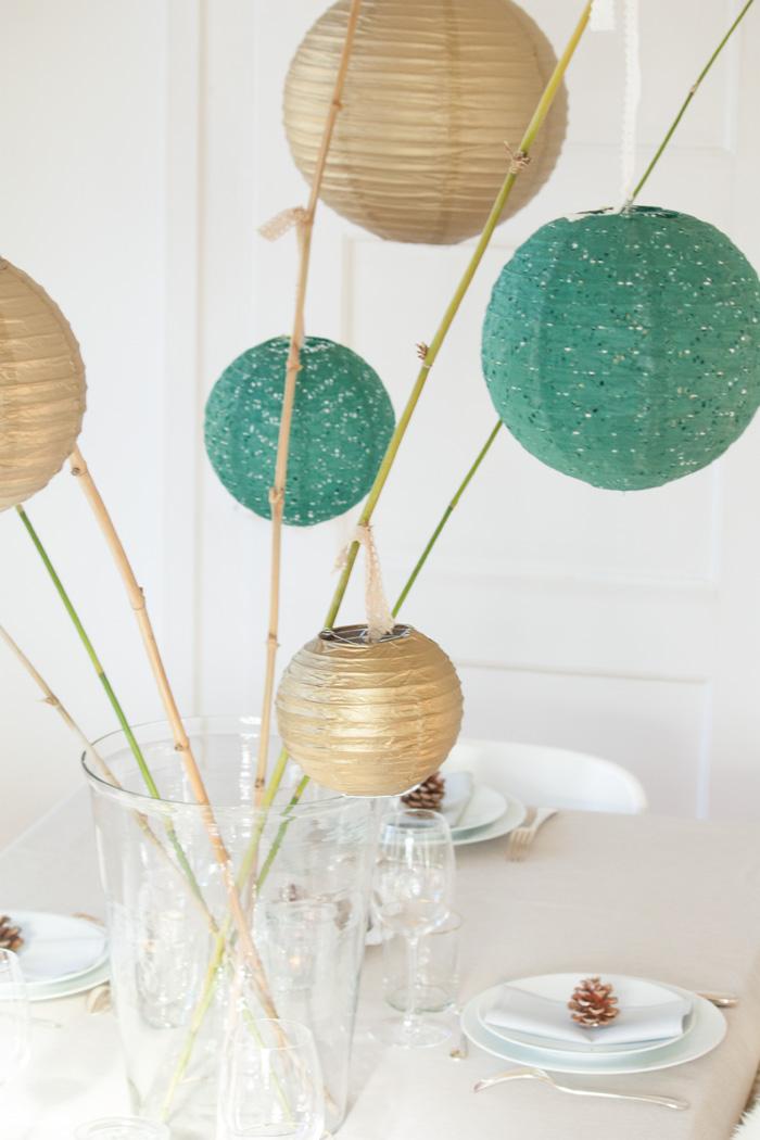 Table de fêtes pour Noel déco lanternes vert et doré dans un vase avec bambou