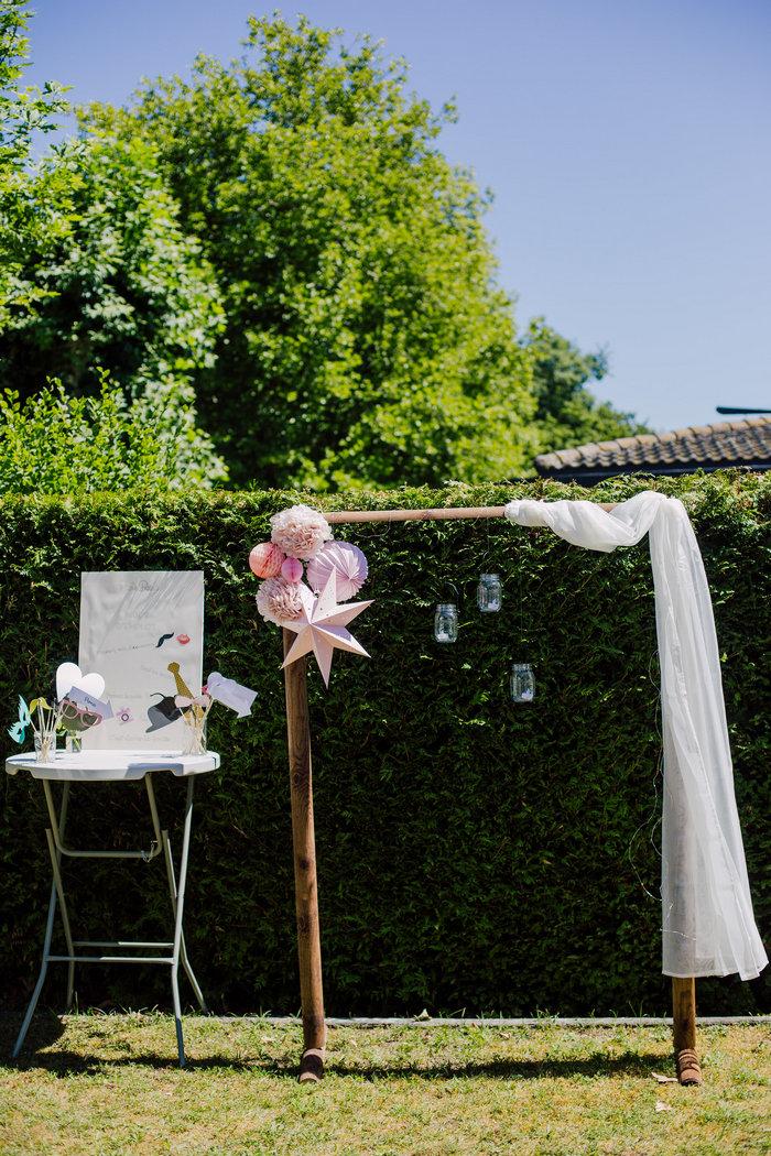 Baptême rose pastel, déco pompon et boule papier rose pour un photobooth