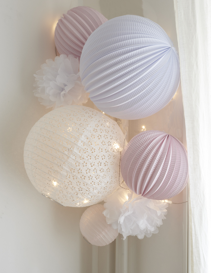 déco blanche et rose pâle pour une chambre de petite fille avec des lanternes et pompons