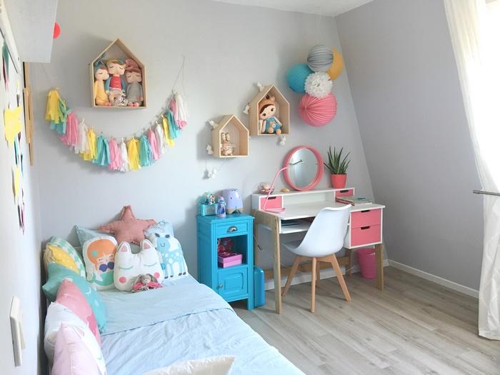 Décoration pastel avec des boules en papier dans cette chambre de fille