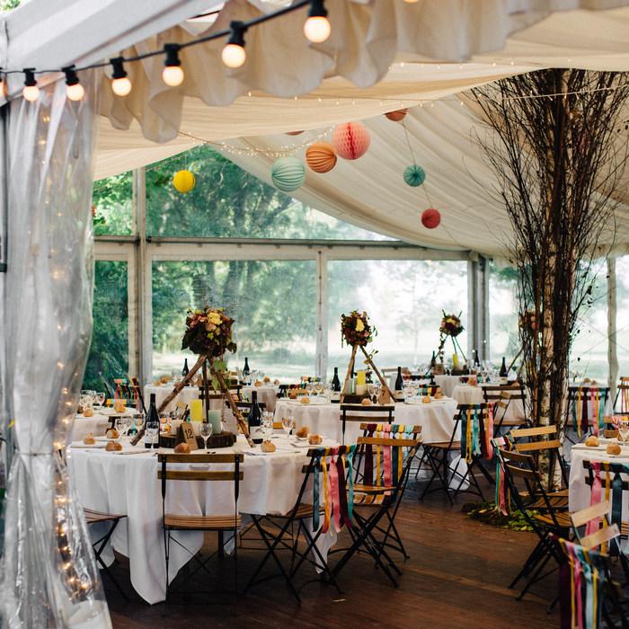 mariage printanier avec des boules en papier sous une tente extérieure