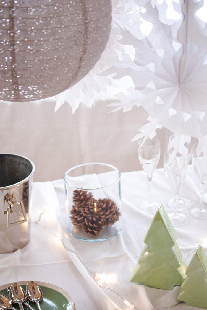 Un buffet de Noël blanc et gris avec des lanternes dentelle et des flocons