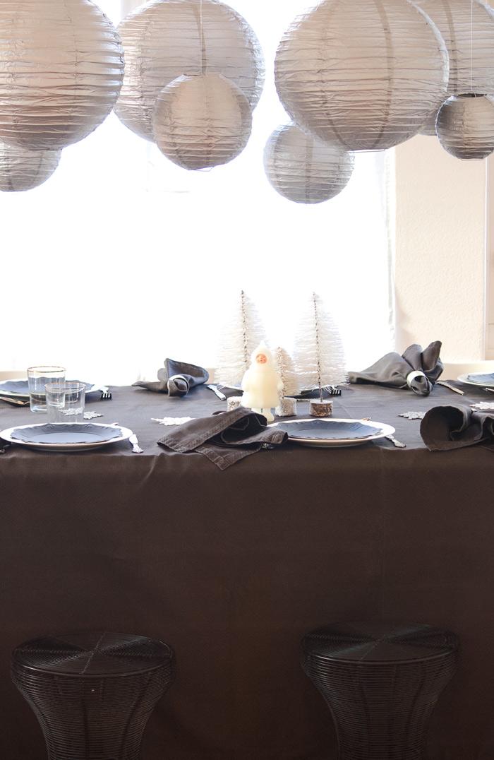 Une table de noël argentée et noire avec des lanternes en papier