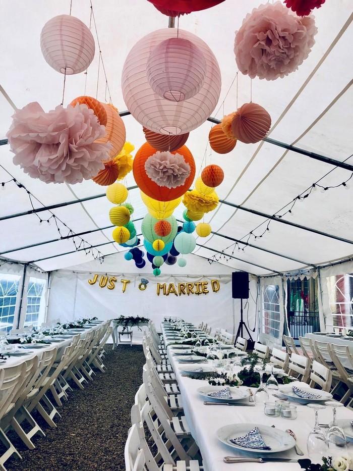 Mariage arc-en-ciel : décoration avec des lanternes en papier coloré dans une tente