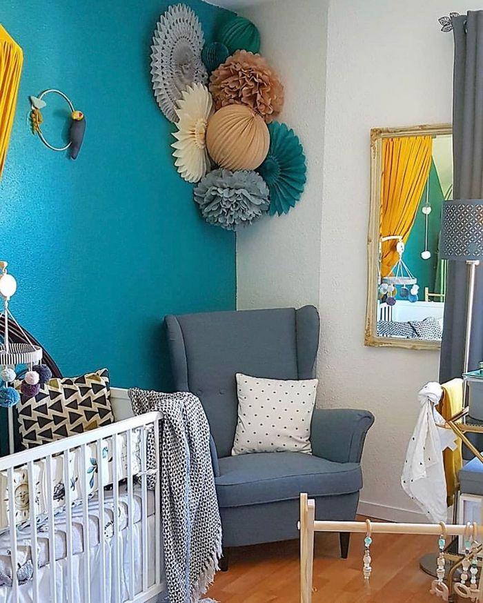 une décoration murale dans un coin de chambre de bébé dans les tons bleu et ocre