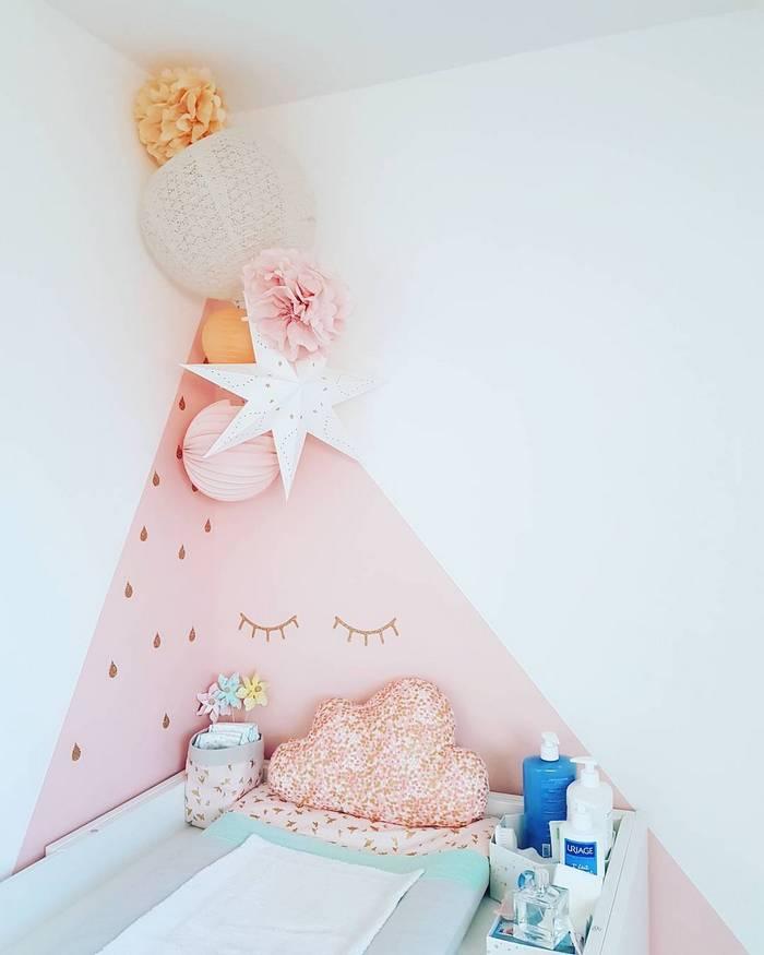 une décoration murale dans un coin de chambre de bébé dans les tons pêche, rose et blanc