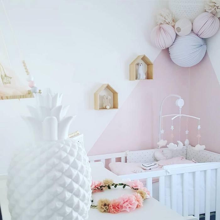 Une décoration murale dans un coin de chambre de bébé dans les tons rose et blanc