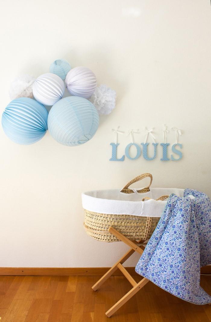 decoration murale bleue avec des lampions et pompons pour une chambre de bébé