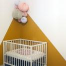 Une chambre de bébé dans les tons moutarde et rose pâle